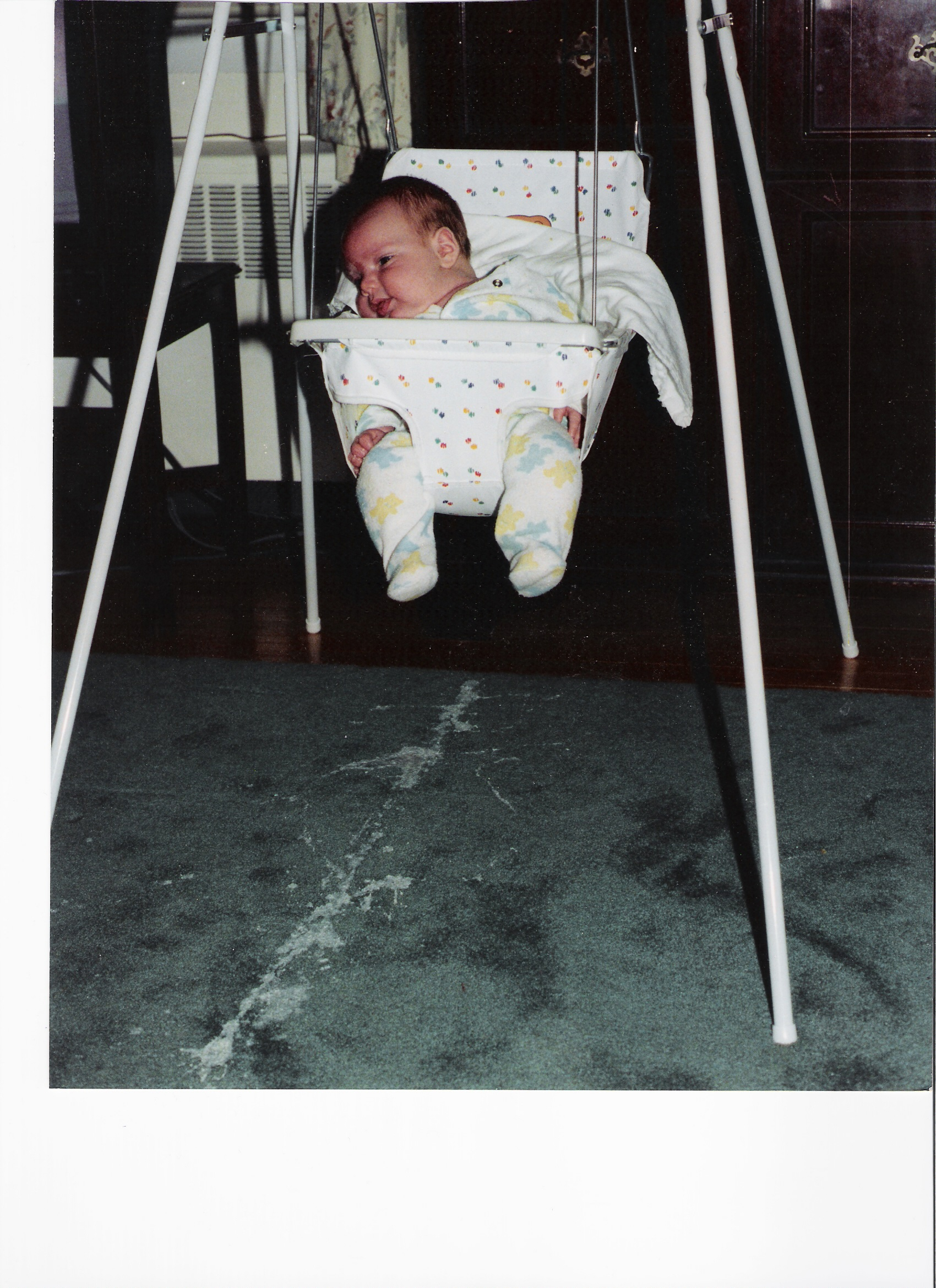 Baby in a swing with a line of vomit on the carpet below